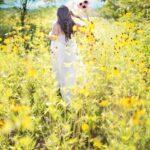 Frau läuft durch Blumenfeld
